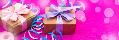 Boîtes de bannière avec des cadeaux sur un fond rose lumineux Photo stock
