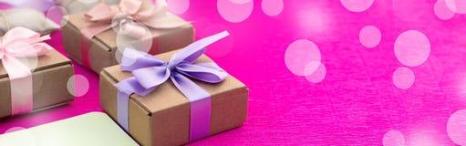 Boîtes de bannière avec des cadeaux sur un fond rose lumineux Photo libre de droits