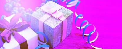 Boîtes de bannière avec des cadeaux sur un fond rose lumineux Photographie stock