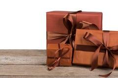 Boîtes de cadeau de Noël enveloppées en papier sur le bois au fond blanc Images libres de droits