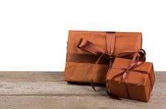 Boîtes de cadeau de Noël enveloppées en papier sur le bois au fond blanc Photos libres de droits