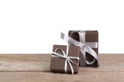 Boîtes de cadeau de Noël enveloppées en papier sur le bois au fond blanc Photo stock