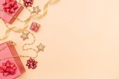 Boîtes de cadeaux ou boîtes de présents avec les arcs, l'étoile et la boule rouges sur le fond d'or pour la cérémonie d'anniversa image stock