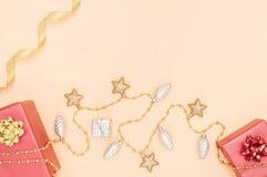 Boîtes de cadeaux ou boîtes de présents avec les arcs, l'étoile et la boule rouges sur le fond d'or pour la cérémonie d'anniversa image libre de droits