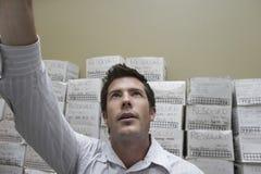 Boîtes de classement d'Against Stack Of d'homme d'affaires photographie stock libre de droits
