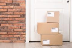 Boîtes de colis de carton sur le plancher près de l'entrée Maquette pour la conception image stock