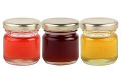 3 boîtes de confitures multicolores et de miel d'isolement sur le fond blanc Images libres de droits