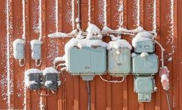 Boîtes de jonction électriques avec la neige, rétro style sur le mur rouge Image stock