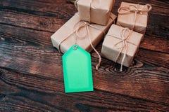 Boîtes de maquette pour des cadeaux des étiquettes de papier et de cadeau d'emballage sur un fond en bois Image libre de droits