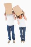 Boîtes de port de couples mûrs au-dessus de leurs têtes Photos stock