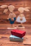 Boîtes de présents devant les couples en bois de lapins de Pâques Images libres de droits