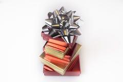 Boîtes de rouge et d'or avec un arc argenté sur un fond d'isolement photographie stock