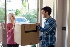 Boîtes de transport de jeunes couples dans la nouvelle maison le jour mobile images stock