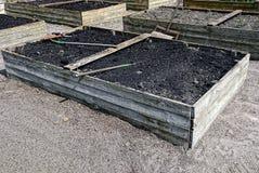 Boîtes en bois avec la terre dans le jardin pour les usines croissantes Photographie stock