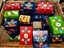 Boîtes en bois faites main colorées dans un grand panier image libre de droits