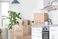 Boîtes en carton et substance de ménage dans la cuisine photos stock