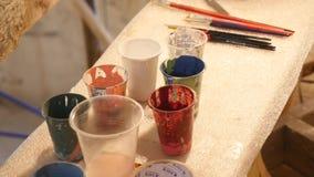Boîtes en plastique multicolores avec des peintures Fond de lieu de travail d'artiste Vieux fond sale de peintures Palette coloré banque de vidéos