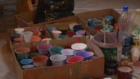 Boîtes en plastique multicolores avec des peintures Fond de lieu de travail d'artiste Vieux fond sale de peintures Palette coloré clips vidéos