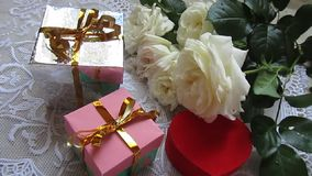 Boîtes et roses de cadeaux banque de vidéos