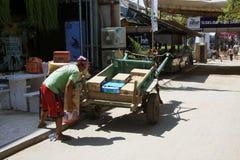Boîtes indonésiennes de chargement d'homme dessus au cheval et au chariot en Gili Trawangan Image libre de droits