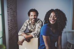 Boîtes mobiles de jeunes couples heureux d'africain noir dans le nouvel appartement ensemble et faisant une vie réussie Famille g Image libre de droits