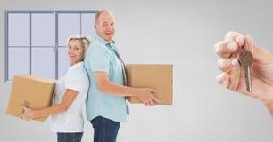 boîtes mobiles de personnes dans la nouvelle maison avec la clé Images stock