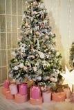 Boîtes roses avec des cadeaux sous l'arbre vert pâle artificiel L'atmosphère à la maison confortable du festival images libres de droits