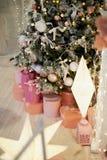 Boîtes roses avec des cadeaux sous l'arbre vert pâle artificiel L'atmosphère à la maison confortable du festival image stock