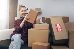 Boîtes s'ouvrantes de femme enthousiaste après la livraison à domicile photo libre de droits