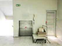 Boîtes sur le chariot devant le mini ascenseur pour la chose de mouvement en haut et en bas Photographie stock