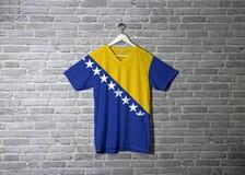 Bośnia i Herzegovina zaznaczamy na koszula i obwieszeniu na ścianie z cegła wzoru tapetą obrazy stock