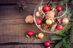 Boże Narodzenia bawją się, dokrętki, jedlinowi rożki i gałązki na drewnianym tle, Zdjęcie Stock