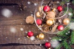 Boże Narodzenia bawją się, dokrętki, jedlinowi rożki i gałązki na drewnianym tle, Fotografia Royalty Free