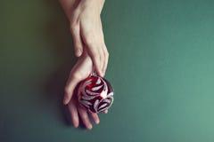 Boże Narodzenia bawją się w pięknych rękach na zielonym tle Obrazy Stock