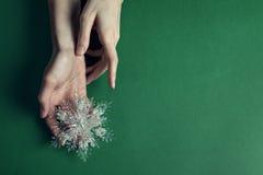 Boże Narodzenia bawją się w pięknych rękach na zielonym tle Zdjęcia Stock