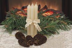Boże Narodzenia Cztery białej wosk świeczki łączącej z openwork faborkiem, jedlinowymi rożkami i sosną, rozgałęziają się na białe zdjęcie royalty free