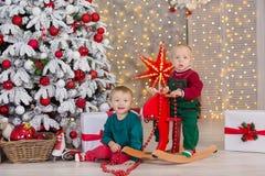 Boże Narodzenia dwa dziecko chłopiec pozuje w pracownianym krótkopędzie blisko do nowego roku aksamita czerwieni i zieleni drzewn zdjęcia royalty free
