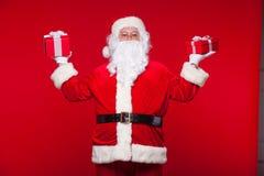 Boże Narodzenia Fotografia Święty Mikołaj daje xmas teraźniejszości i patrzeje kamerę, na czerwonym tle zdjęcia stock