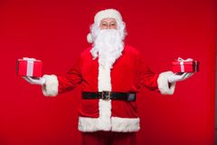 Boże Narodzenia Fotografia Święty Mikołaj daje xmas teraźniejszości i patrzeje kamerę, na czerwonym tle obrazy stock