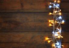 Boże Narodzenia grżą złocistych girland światła na drewnianym nieociosanym tle Filtrujący wizerunek Fotografia Royalty Free