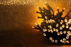 Boże Narodzenia grżą złocistych girland światła na drewnianym nieociosanym tle Filtrujący wizerunek Fotografia Stock
