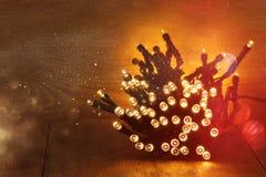Boże Narodzenia grżą złocistych girland światła na drewnianym nieociosanym tle Filtrujący wizerunek Zdjęcie Royalty Free