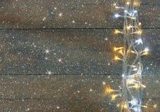 Boże Narodzenia grżą złocistych girland światła na drewnianym nieociosanym tle filtrujący wizerunek z błyskotliwości narzutą Obrazy Stock