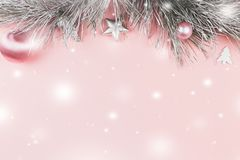 Boże Narodzenia graniczą z jedlinowymi gałąź, boże narodzenie piłkami i srebro ornamentami na pastelowych menchii tle, śnieżny sp fotografia royalty free
