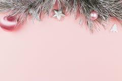 Boże Narodzenia graniczą z jedlinowymi gałąź, boże narodzenie piłkami i srebro ornamentami na pastelowych menchii tle, zdjęcie stock