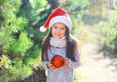 Boże Narodzenia i ludzie pojęć - małej dziewczynki dziecko w Santa czerwonym kapeluszu z piłką Obrazy Royalty Free