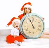 Boże Narodzenia i ludzie pojęć - matka z dzieckiem i zegarem Zdjęcie Stock