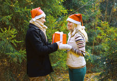 Boże Narodzenia i ludzie pojęć - obsługuje dawać pudełkowatemu prezentowi kobieta fotografia stock