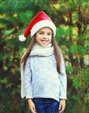 Boże Narodzenia i ludzie pojęć - uśmiechnięty małej dziewczynki dziecko w Santa czerwieni kapeluszu Zdjęcie Royalty Free