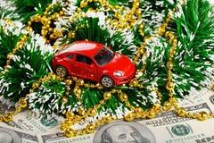Boże Narodzenia i nowego roku czerwony samochód bawją się przez dolarów Zdjęcia Stock